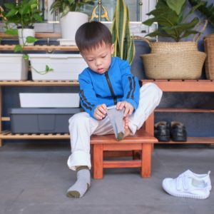 Cute little Asian 3 years old toddler kindergarten kid sitting near shoe rack near front door of his house and concentrate on putting on his own socks, Encourage Self-Help Skills in Children concept
