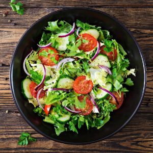 Salad from tomatoes, cucumber, red onions and lettuce leaves. Healthy summer vitamin menu. Vegan vegetable food. Vegetarian dinner table. Top view. Flat lay